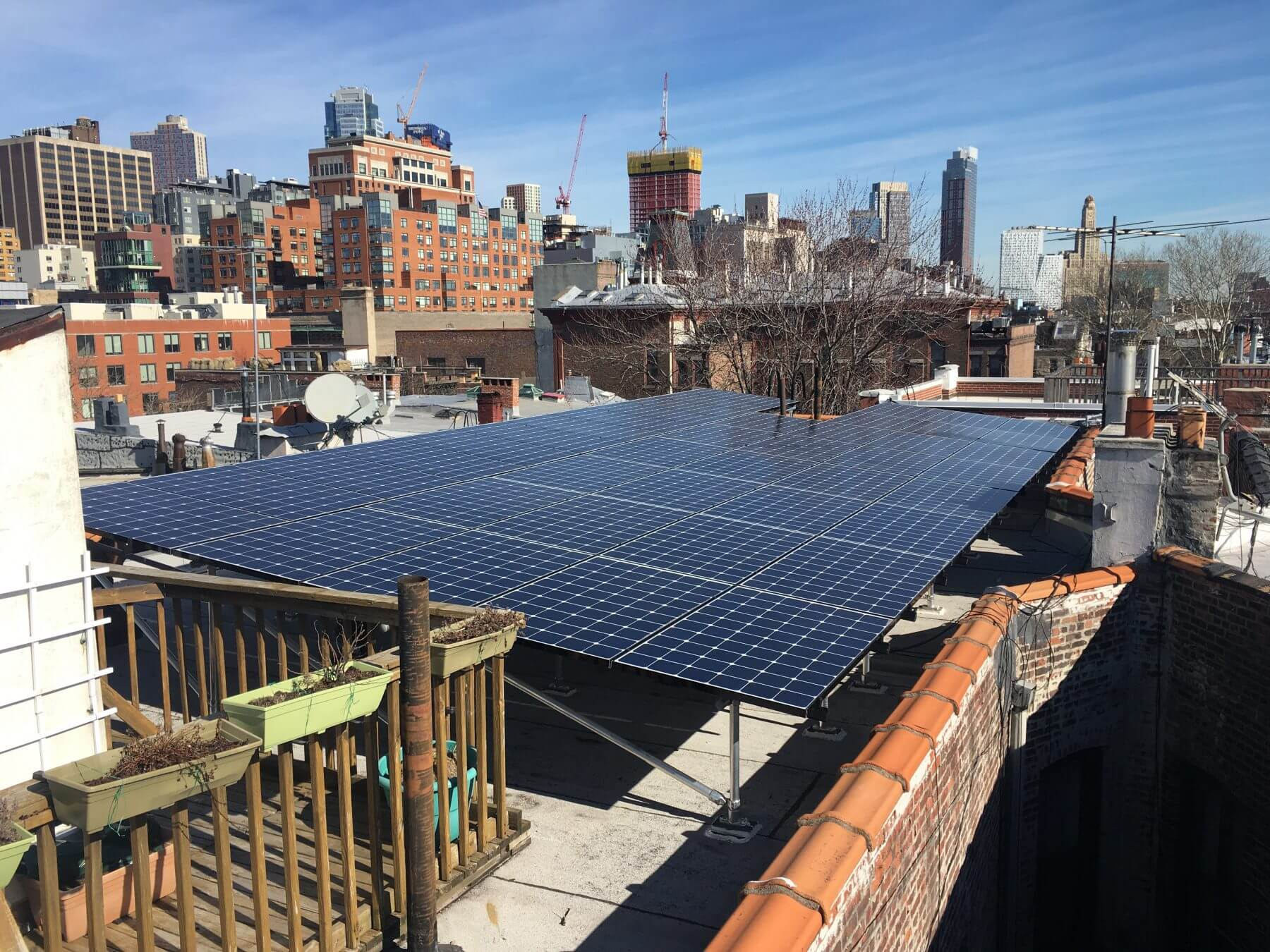 A tilt rack solar system installed next to an existing deck on a 10-unit, landmarked co-op in Cobble Hill.