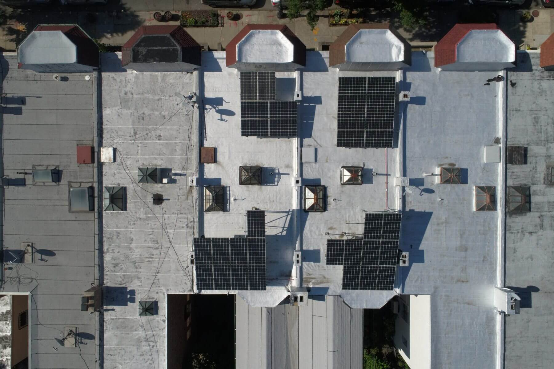 Two tilt rack solar systems designed around hatches and sky lights (Lefferts Gardens).